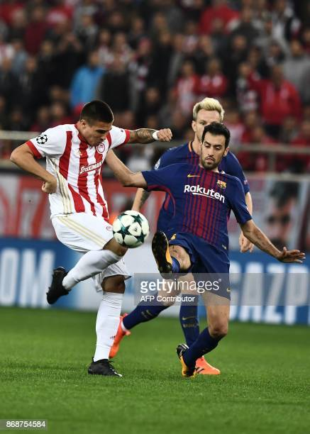 Barcelona's Spanish midfielder Sergio Busquets vies with Olympiakos' Serbian forward Uros Djurdjevic during the UEFA Champions League group D...