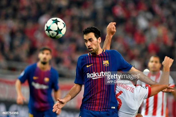 Barcelona's Spanish midfielder Sergio Busquets vies with Olympiakos' midfielder Panagiotis Tachtsidis during the UEFA Champions League group D...