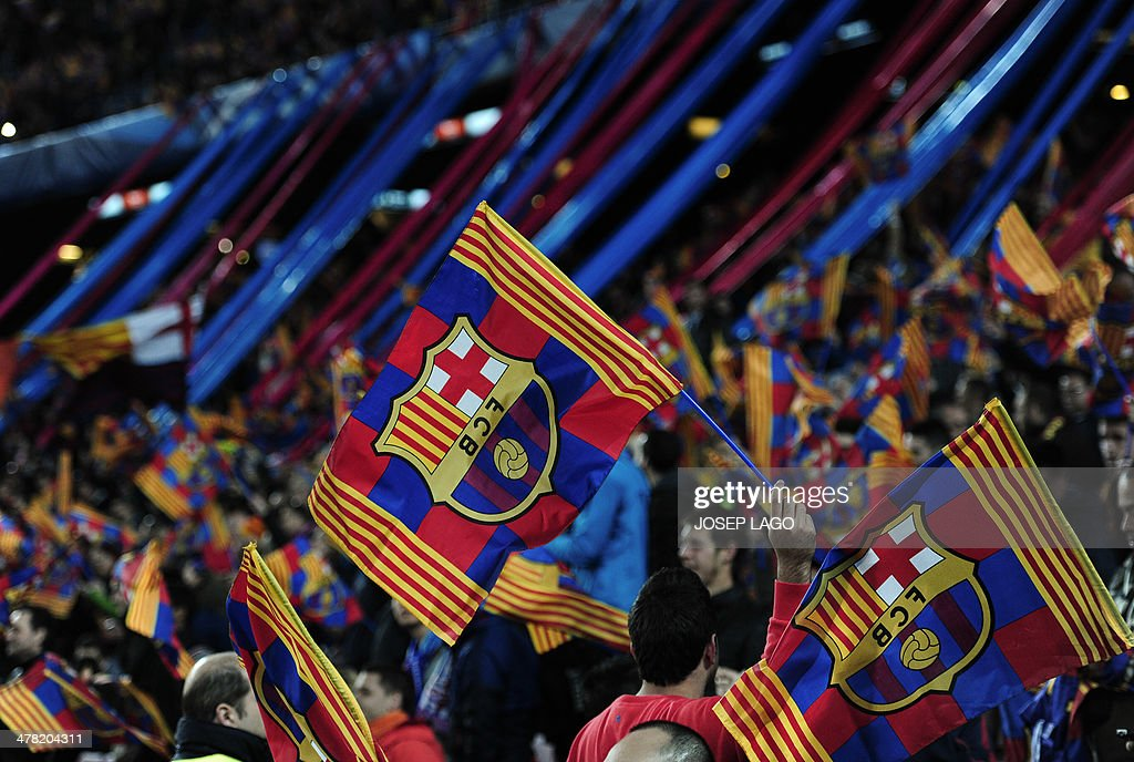 FC Barcelona's supporters wave their club's flag during the UEFA Champions League round of 16 second leg football match FC Barcelona vs Manchester City at the Camp Nou stadium in Barcelona on March 12, 2014.