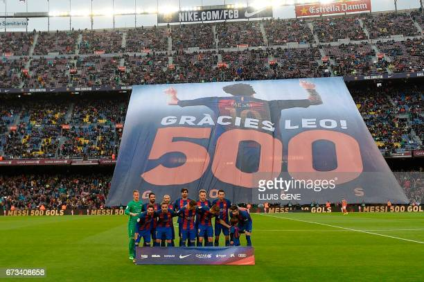 Barcelona's team poses as a banner is unfurled in tribute to Argentinian forward Lionel Messi for his 500th goal for the club before the Spanish...