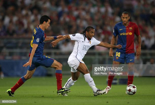 Barcelona's Thierry Henry looks on as teammate Sergio Busquets and Manchester United's Oliveira Anderson battle for the ball