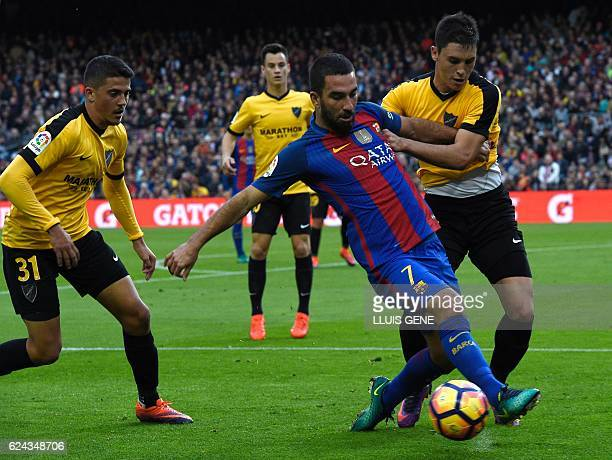 Barcelona's Turkish forward Arda Turan vies with Malaga's defender Diego Llorente during the Spanish league football match between FC Barcelona and...