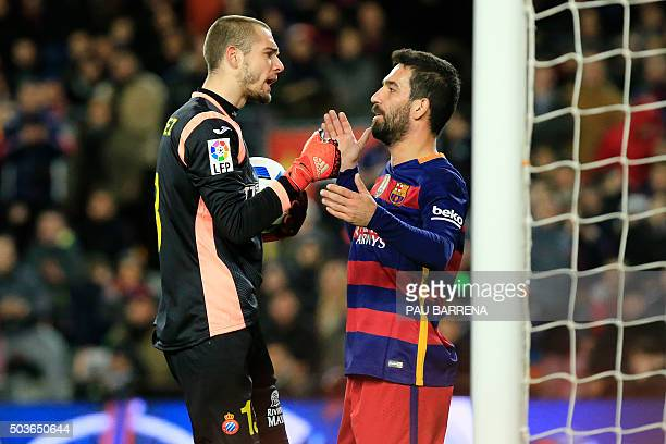 Barcelona's Turkish midfielder Arda Turan argues with RCD Espanyol's Spanish goalkeeper Pau Lopez during the Spanish Copa del Rey round of 16 first...