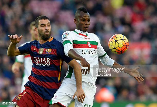 Barcelona's Turkish midfielder Arda Turan vies with Granada's Nigerian midfielder Uche during the Spanish league football match FC Barcelona vs...