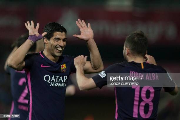 Barcelona's Uruguayan forward Luis Alberto Suarez celebrates with defender Jordi Alba after scoring during the Spanish league football match Granada...