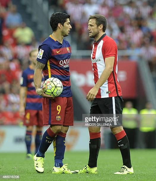 Barcelona's Uruguayan forward Luis Suarez and Athletic Bilbao's midfielder Carlos Gurpegi react during the Spanish league football match Athletic...