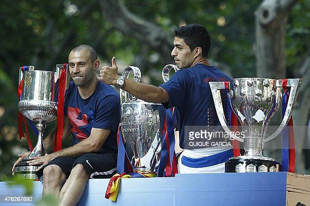 Barcelona's Uruguayan forward Luis Suarez and Barcelona's Argentinian defender Javier Mascherano pose with the three trophies on a bus parading...