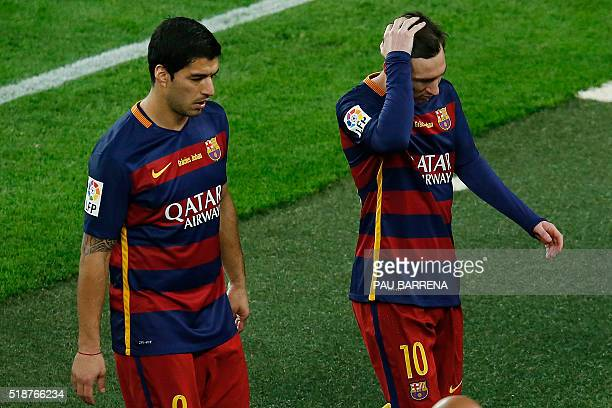 Barcelona's Uruguayan forward Luis Suarez and Barcelona's Argentinian forward Lionel Messi leave the field after losing the Spanish league 'Clasico'...