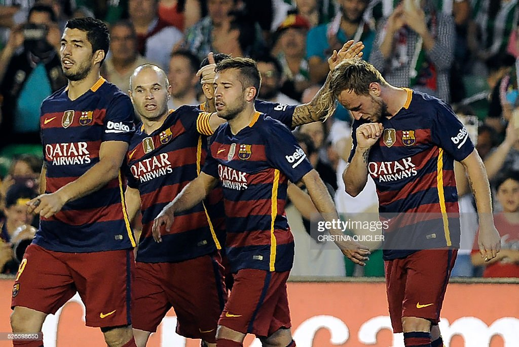 Barcelona's Uruguayan forward Luis Suarez (L) and Barcelona's midfielder Andres Iniesta (2nd L) walk with Barcelona's Croatian midfielder Ivan Rakitic (R) as he celebrates a goal during the Spanish league football match Real Betis Balompie vs FC Barcelona at the Benito Villamarin stadium in Sevilla on April 30, 2016. / AFP / CRISTINA