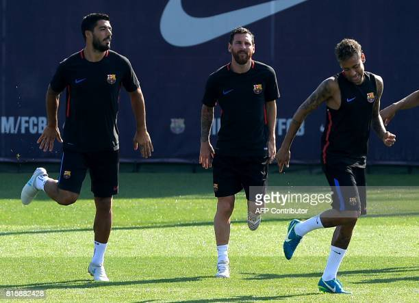 Barcelona's Uruguayan forward Luis Suarez Barcelona's Argentinian forward Lionel Messi and Barcelona's Brazilian forward Neymar warm up during a...