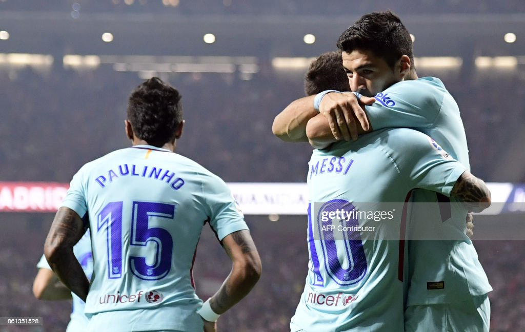 Barcelona's Uruguayan forward Luis Suarez (R) celebrates a goal with Barcelona's Argentinian forward Lionel Messi during the Spanish league football match Club Atletico de Madrid vs FC Barcelona at the Wanda Metropolitano stadium in Madrid on October 14, 2017. /