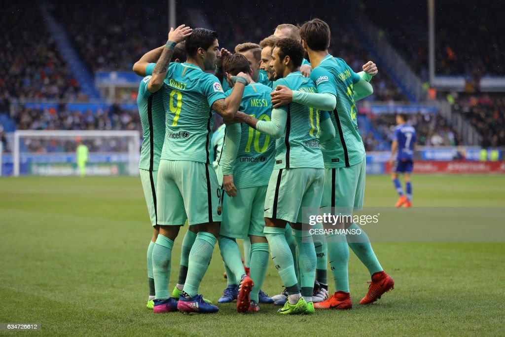 Barcelona's Uruguayan forward Luis Suarez (L) celebrates a goal with teammates during the Spanish league football match Deportivo Alaves vs FC Barcelona at the Mendizorroza stadium in Vitoria on Feburary 11, 2017. / AFP / CESAR