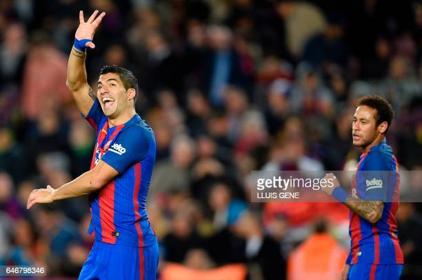 TOPSHOT Barcelona's Uruguayan forward Luis Suarez celebrates past Barcelona's Brazilian forward Neymar after scoring during the Spanish league...
