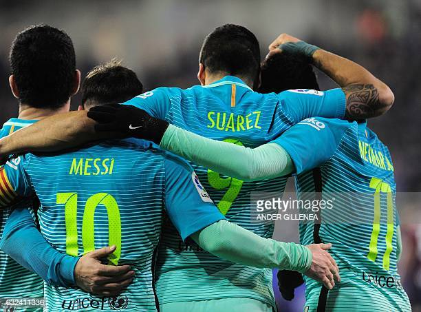 Barcelona's Uruguayan forward Luis Suarez celebrates with teammates after scoring his team's third goal during the Spanish league football match SD...