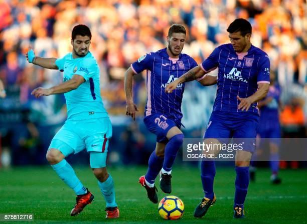 Barcelona's Uruguayan forward Luis Suarez challenges Leganes' Spanish midfielders Gerard Gumbau and Ruben Perez during the Spanish league football...