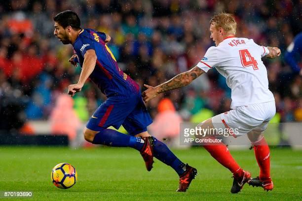 Barcelona's Uruguayan forward Luis Suarez challenges Sevilla's Danish defender Simon Kjaer during the Spanish league football match FC Barcelona vs...