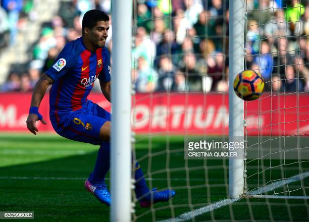 Barcelona's Uruguayan forward Luis Suarez eyes the ball as he scores a goal during the Spanish league football match Real Betis vs FC Barcelona at...