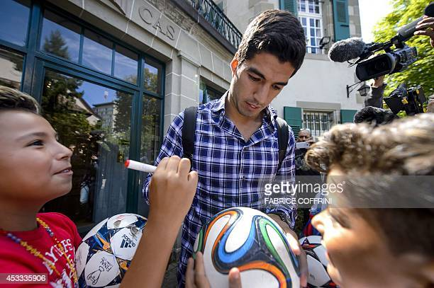 Barcelona's Uruguayan forward Luis Suarez is surrounded by fans after he pleaded his case before the Court of Arbitration for Sport to halve his...