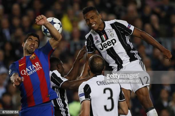 Barcelona's Uruguayan forward Luis Suarez Juventus' defender Giorgio Chiellini and Juventus' Brazilian defender Alex Sandro go up for a header during...