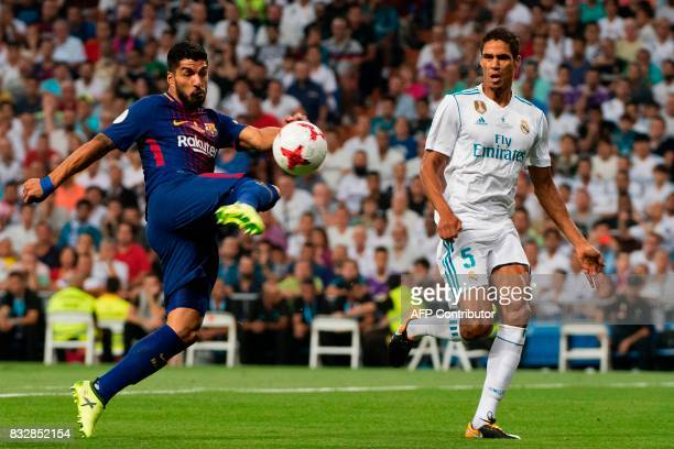 Barcelona's Uruguayan forward Luis Suarez kicks the ball past Real Madrid's French defender Raphael Varane during the second leg of the Spanish...