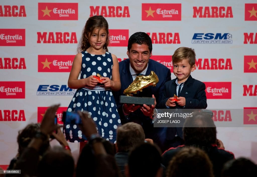 TOPSHOT - Barcelona's Uruguayan forward Luis Suarez (C) poses with his children Delfina (L) and Benjamin, after receiving the 2015-2016 Golden Shoe award to the leading goalscorer in league matches from the top division of every European national league, on October 20, 2016 in Barcelona. / AFP / JOSEP