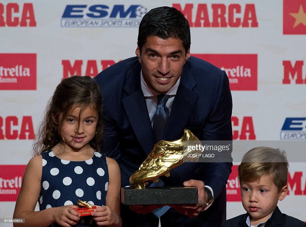 Barcelona's Uruguayan forward Luis Suarez (C) poses with his children Delfina (L) and Benjamin, after receiving the 2015-2016 Golden Shoe award to the leading goalscorer in league matches from the top division of every European national league, on October 20, 2016 in Barcelona. / AFP / JOSEP