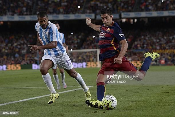 Barcelona's Uruguayan forward Luis Suarez prepares to kick the ball past Malaga's Argentinian midfielder Fernando Damian Tissone during the Spanish...
