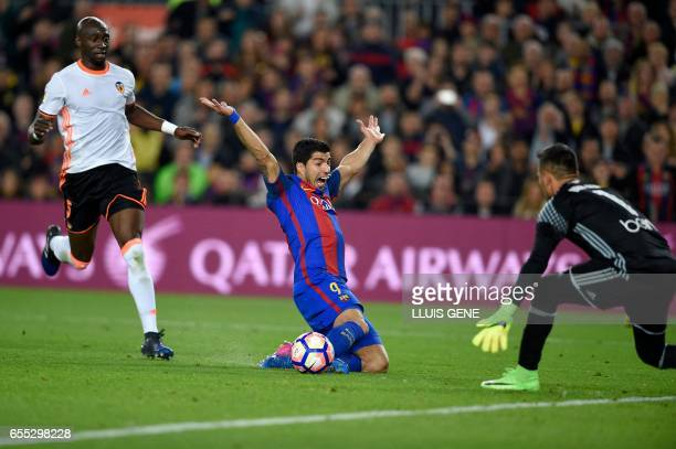Barcelona's Uruguayan forward Luis Suarez receives a penalty from play by Valencia's Brazilian defender Eleaquim Mangala during the Spanish league...