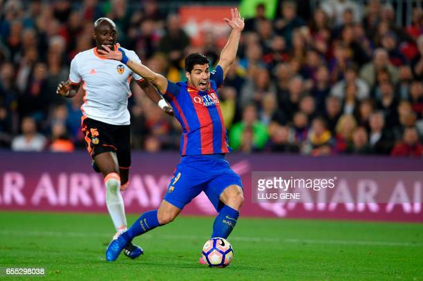 Barcelona's Uruguayan forward Luis Suarez receives a penalty from plya by Valencia's Brazilian defender Eleaquim Mangala during the Spanish league...