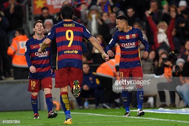Barcelona's Uruguayan forward Luis Suarez runs to celebrate a goal with Barcelona's Brazilian forward Neymar and Barcelona's Argentinian forward...