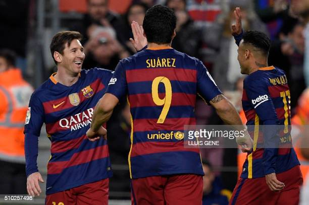 Barcelona's Uruguayan forward Luis Suarez runs to celebrate a goal with Barcelona's Brazilian forward Neymar and Barcelona's Argentinian forward...