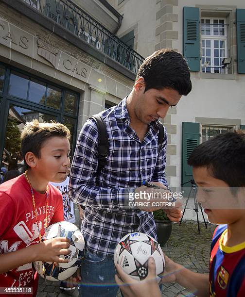 Barcelona's Uruguayan forward Luis Suarez signs autographs for young fans after he pleaded his case before the Court of Arbitration for Sport to...