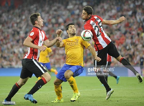 Barcelona's Uruguayan forward Luis Suarez vies with Athletic Bilbao's defender Aymeric Laporte and Sabin Merino during the Spanish Supercup firstleg...
