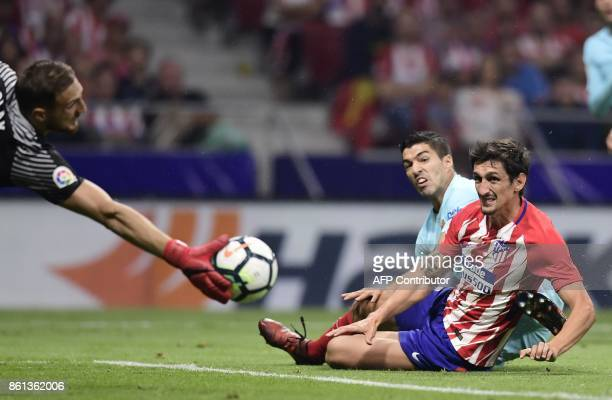 Barcelona's Uruguayan forward Luis Suarez vies with Atletico Madrid's Montenegrin defender Stefan Savic during the Spanish league football match Club...