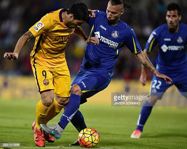 Barcelona's Uruguayan forward Luis Suarez vies with Getafe's defender Alexis Ruano during the Spanish league football match Getafe CF vs FC Barcelona...