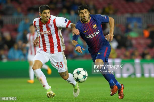 Barcelona's Uruguayan forward Luis Suarez vies with Olympiacos' Greek defender Dimitris Nikolaou during the UEFA Champions League group D football...