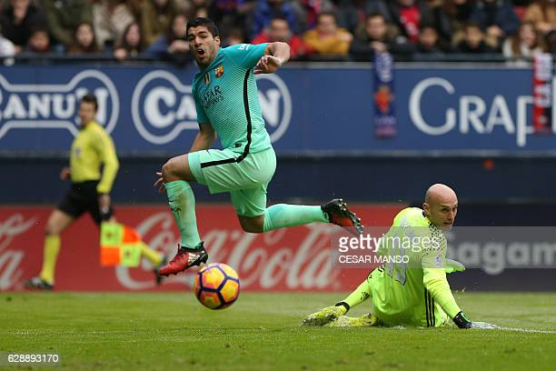 Barcelona's Uruguayan forward Luis Suarez vies with Osasuna's goalkeeper Nauzet Perez during the Spanish league football match CA Osasuna vs FC...
