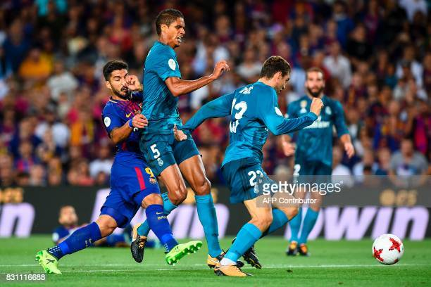 Barcelona's Uruguayan forward Luis Suarez vies with Real Madrid's French defender Raphael Varane and Real Madrid's Croatian midfielder Mateo Kovacic...