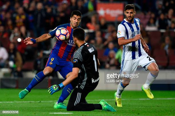 Barcelona's Uruguayan forward Luis Suarez vies with Real Sociedad's Argentinian goalkeeper Geronimo Rulli and Real Sociedad's Brazilian forward Raul...