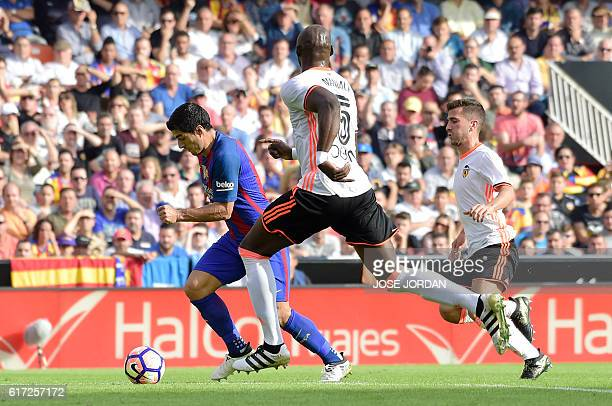 Barcelona's Uruguayan forward Luis Suarez vies with Valencia's French defender Eliaquim Mangala during the Spanish league football match between...