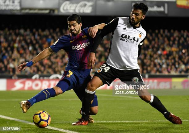 Barcelona's Uruguayan forward Luis Suarez vies with Valencia's Argentinian defender Ezequiel Garay during the Spanish league football match Valencia...