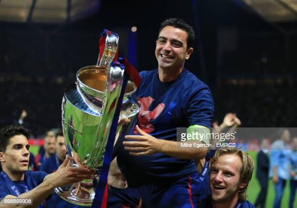 Barcelona's Xavi Hernandez celebrates with the UEFA Champions League Trophy with teammates Ivan Rakitic and Marc Bartra