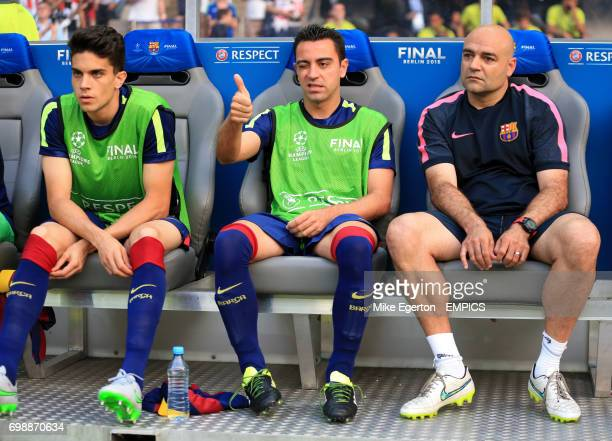 Barcelona's Xavi Hernandez gives a thumbs up from the bench as he sits next to coach Jos Ramon de la Fuente and teammate Marc Bartra