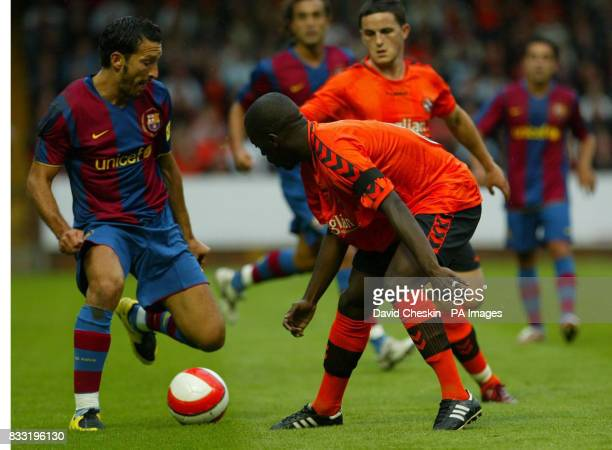 Barcelona's Zambrotta holds off Dundee United's Morgaro Gomis during the preseason friendly match at Tannadice Park Dundee