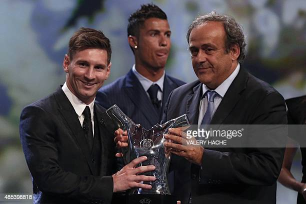 FC Barcelone Argentinian striker Lionel Messi receives from UEFA president Michel Platini the trophy of Best Men's player in Europe next to runnerup...