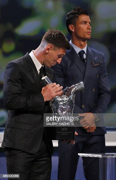 FC Barcelone Argentinian striker Lionel Messi receives the trophy of Best Men's player in Europe next to runnerup Portugal's Cristiano Ronaldo at the...