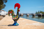 Rooster of Barcelos (Galo de Barcelos) on a quay of river Gilao. Tavira, Algarve, Portugal
