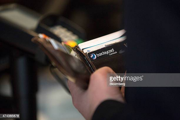 A Barclaycard bank card issued by Barclays Plc is seen in a customer's wallet as they prepare to pay the bill at a restaurant in London UK on Friday...