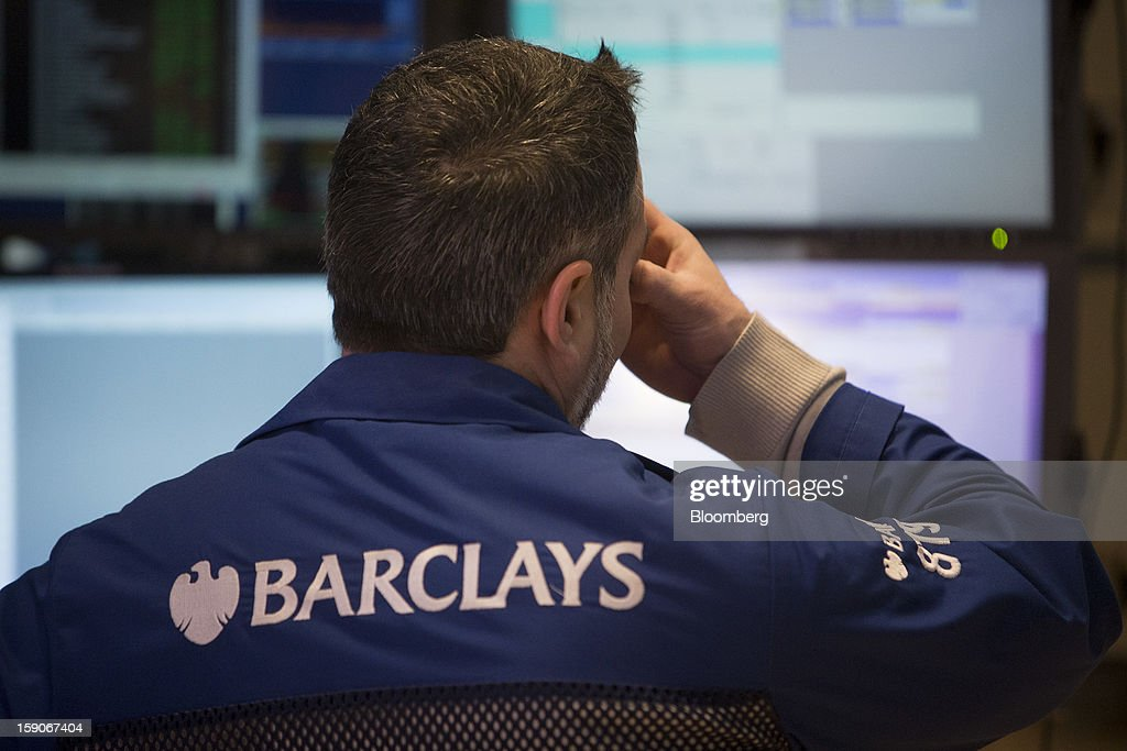 A Barclays PLC trader holds a hand to his face while working on the floor of the New York Stock Exchange (NYSE) in New York, U.S., on Monday, Jan. 7, 2013. U.S. stocks fell, after the Standard & Poor's 500 Index climbed to a five-year high, as investors awaited the start of the corporate earnings season tomorrow. Photographer: Scott Eells/Bloomberg via Getty Images