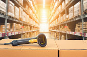 Barcode scanner in front of modern warehouse and scanning code on cardboard box